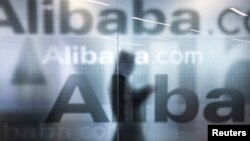 An employee walks behind glass door of Alibaba's company headquarters near Hangzhou, Zhejiang province. The company is expected to sell its stock to the public in an Initial Public Offering (IPO) on the New York Stock Exchange.