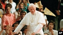 In a Sept. 15, 1987 file photo, Pope John Paul II walks among young people at the Universal Amphitheatre in Los Angeles, California.