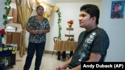 Ajuda Thapa, left, stands near her son, Jay Thapa, in their home in Burlington, Vt. Ajuda Thapa, 45, a former refugee from Bhutan, participates in a program for torture survivors at the University of Vermont