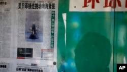 Bóng một người đàn ông Trung quốc phản ánh trên cửa kính cho thấy ông đang đọc tờ Hoàn cầu Thời báo vốn có lập trường cứng rắn và do Nhân dân Nhật báo - cơ quan ngôn luận của Đảng Cộng Sản TQ quản lý, nói về tranh chấp Biển Đông. (AP Photo/Andy Wong)