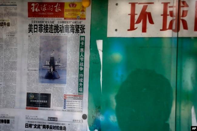 资料照:北京街头一名男子在读一处报栏里张贴的环球时报。 (2016年4月5日)