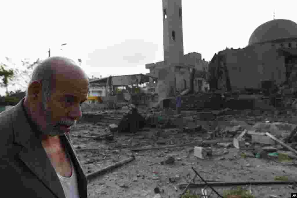 Palestinian Khaled Sharmi, 67, walks past the Al Aqsa Martyrs mosque, destroyed by an overnight Israeli strike, in Gaza City, July 22, 2014.