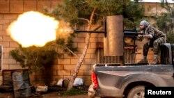 Un combatiente juro dispara un cañon antiaéreo contra posiciones del grupo Estado islámico en la aldea de Tel Tawill en Siria.