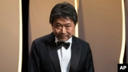 "Director Hirokazu Kore-eda bows to the audience after winning the Palme d'Or for the film ""Shoplifters"" during the closing ceremony of the 71st international film festival, Cannes, southern France, May 19, 2018."