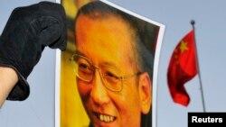 一位抗議者在中國駐奧斯陸大使館門外舉著劉曉波的照片 (資料圖片)