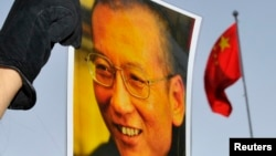 FILE - A protester holds an image of to jailed dissident Liu Xiaobo outside of the Chinese Embassy in Oslo, Dec. 9, 2010.
