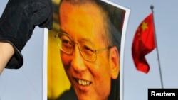 一位抗議者在中國駐奧斯陸大使館門外舉著劉曉波的照片。(資料圖片)