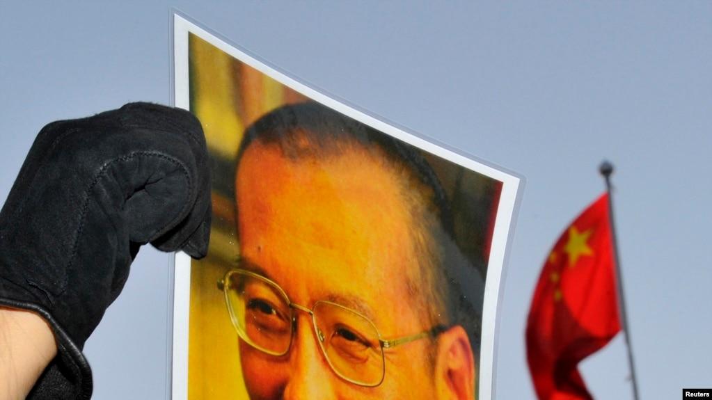 一位抗议者在中国驻奥斯陆大使馆门外举着刘晓波的照片。(资料照)