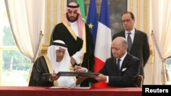 French Foreign Minister Laurent Fabius (R), exchanges documents with Dr. Hashim Yamani, the President of King Abdullah City for Atomic and Renewable Energy, after signing an agreement between France and Saudi Arabia, at the Elysee Palace in Paris, June 24, 2015.