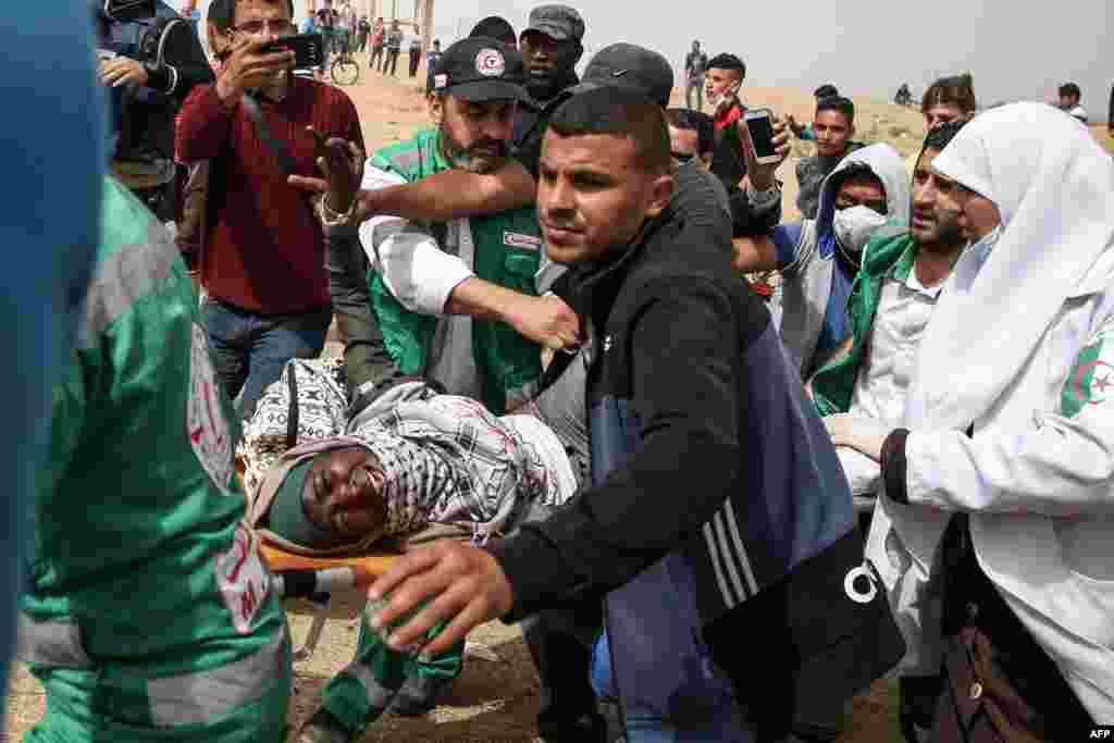 팔레스타인 가자지구에서 이스라엘군과 팔레스타인의 충돌이 있은 후, 팔레스타인 의료진들이 부상한 여성을 실어 나르고 있다.