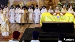 FILE - Orthodox Patriarch Alexiy II (L) leads a mourning ceremony at the coffin of Empress Maria Fyodorovna, the wife of Tsar Alexander III and mother of Russia's last monarch, Nicholas II, in St. Isaac's cathedral in St. Petersburg, Sept. 28, 2006. Russian investigators say they plan to exhume the remains of Tsar Alexander III at the request of the Orthodox Church to authenticate the remains of his son, the murdered last tsar, and his slain children.