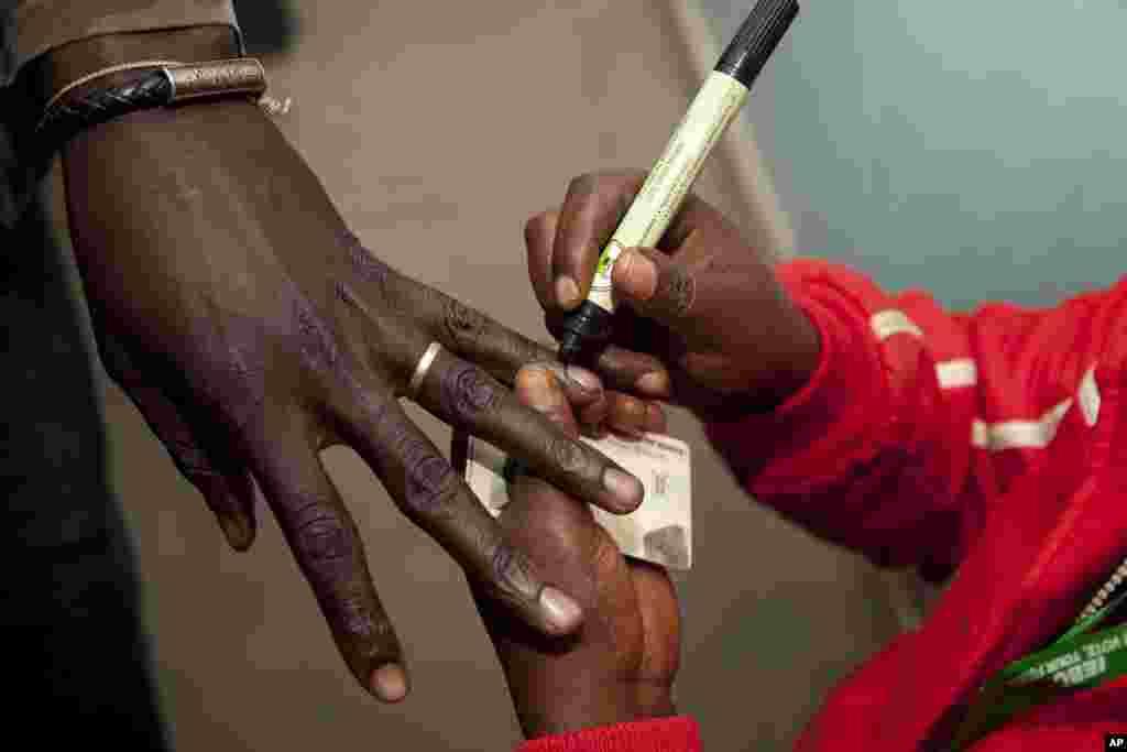 په کینیا کې د رایې ورکولو د حوزې یو کارکونکی د یوه رایه ورکونکي د ګوتې د رنګولو په حال کې