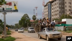 FILE PHOTO - Cambodian passengers sit on top of a pickup truck driven past an unfinished building in Phnom Penh, Cambodia, Monday, Sept. 3, 2007.