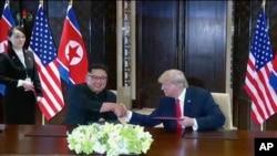 Prezidan Donald Trump (adwat) nan somè ki te mete l kòt-a-kòt avèk lidè Kore di Nò a, Kim Jong Un, nan Sengapou nan dat 12 jen 2018 la.