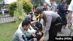 Polisi geledah peserta aksi 112 dari Solo yang akan berangkat ke Jakarta (Foto: VOA/Yudha)
