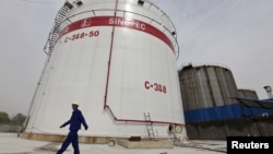 FILE - An employee walks past oil tanks at a Sinopec refinery in Wuhan, Hubei province April 25, 2012. China's top state-owned refiners have decided not to order any oil for loading at Iranian ports this month, according to Reuters.