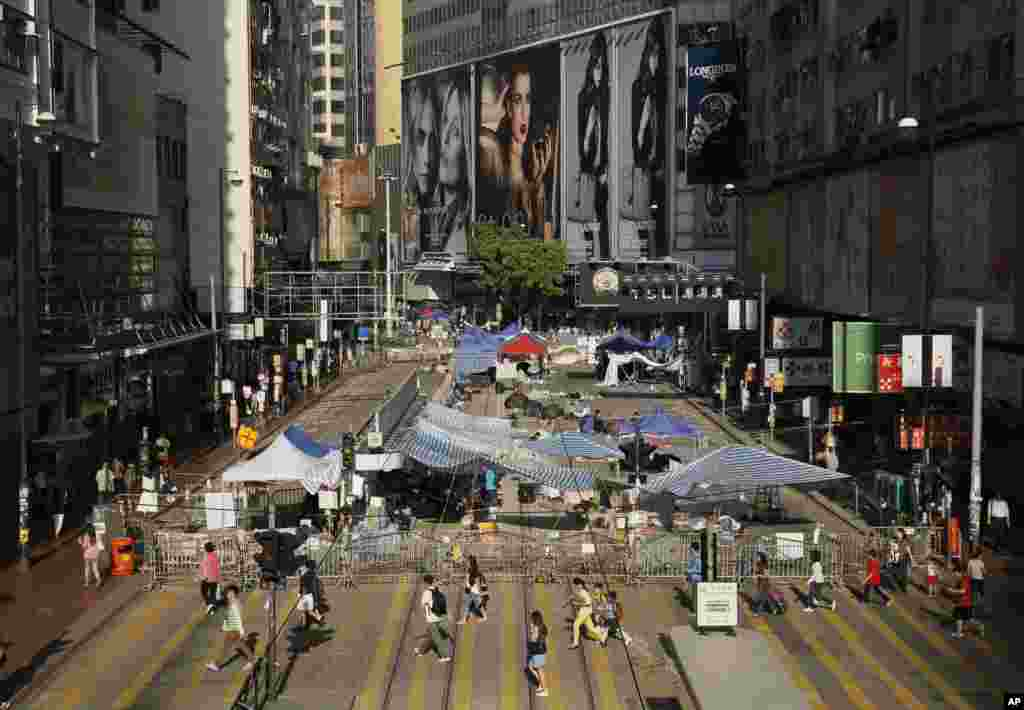 Students walk past barricades on a main road in the occupied areas of the Causeway Bay district in Hong Kong, Oct. 10, 2014.