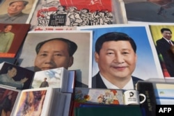 Posters of Chinese President Xi Jinping (R) and late communist leader Mao Zedong are seen at a market in Beijing on February 26, 2018.