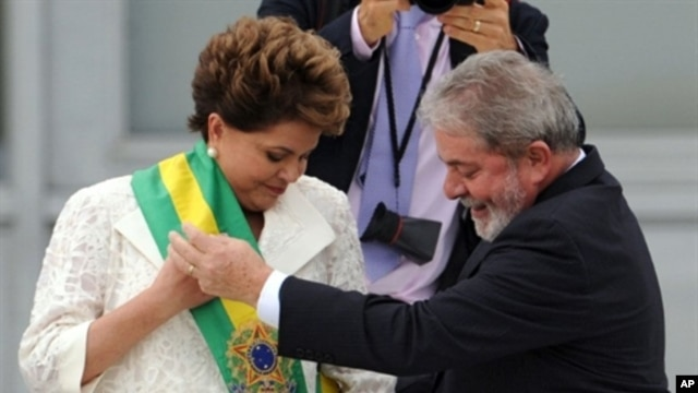 Newly sworn-in Brazilian President Dilma Rousseff (L) receives the presidential sash from outgoing President Luiz Inacio Lula da Silva at the Planalto Palace in Brasilia, 1 Jan 2011