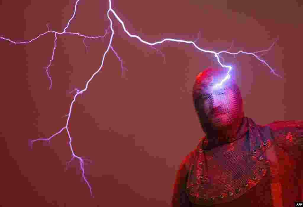 """Seorang pria tampak disambar oleh """"petir"""" buatan di sebuah museum fenomena sains """"Phaeno"""" di kota Wolfsburg, Jerman."""