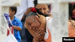 Denise Paba, who lost her 6-year-old niece Veronica Moser, is comforted as she cries at a memorial for victims behind the theatre where a gunman opened fire last Friday on moviegoers in Aurora, Colorado July 22, 2012.