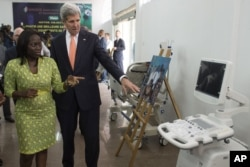 FILE - Then-U.S. Secretary of State John Kerry and entrepreneur Patricia Nzolantima point at an ultrasound machine during a tour of a Sustainable Investment in Sub-Saharan Africa medical supply store in Kinshasa, DRC, May 3, 2014.