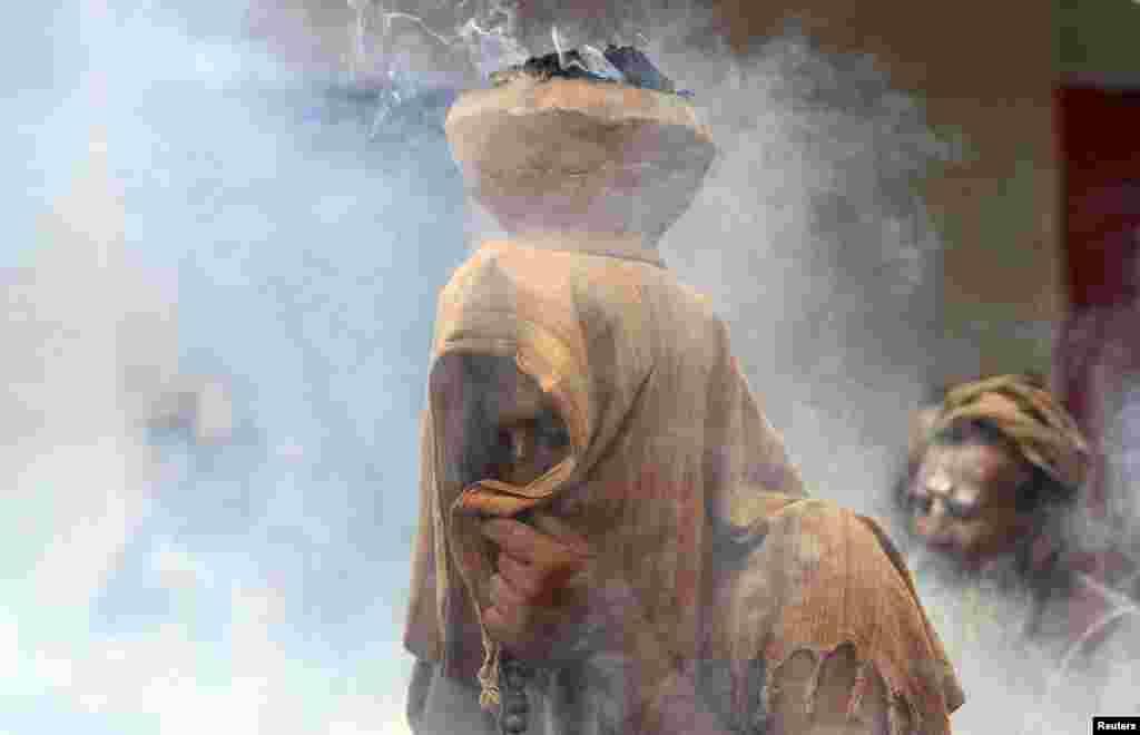 បុរសកាន់ជំនឿសាសនាហិណ្ឌូគ្របមុខរបស់ខ្លួន ជាមួយនឹងឆ្នាំដីដាក់អាចម៌គោសម្ងួតដែលកំពុងឆេះនៅលើក្បាលរបស់ខ្លួននៅអំឡុងពេលពិធីបួងសួងនៅក្នុងពិធីបុណ្យ Simhastha Kumbh Mela ក្នុងក្រុង Ujjain ប្រទេសឥណ្ឌា។