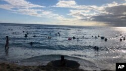 In this photo taken May 13, 2020 in Honolulu, people are in the water at a Waikiki beach.