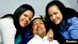 Hugo Chavez diapit oleh dua putrinya, Rosa Virginia (kanan) dan Maria setelah sebuah operasi di Havana, untuk kanker yang dideritanya.
