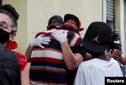 "Flavio Falcone hugs a man as Andrea Macera, talks to other men as they check on people in an area known as ""cracolandia"" in the historic center of Sao Paulo, Brazil, February 9, 2021. REUTERS/Amanda Perobelli"