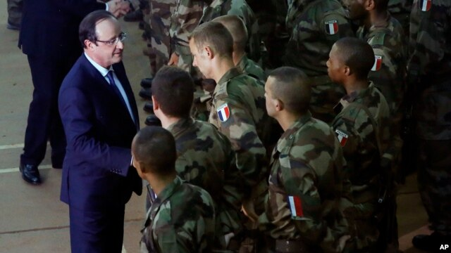 French President Francois Hollande, left,  addresses the troops during a stopover from South Africa in Bangui, CAR, Dec. 10, 2013.