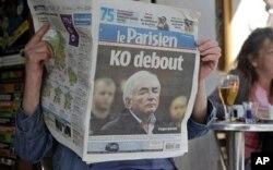 """Une femme lisant le journal """"Le Parisien"""" consacré à l'affaire Strauss-Kahn"""