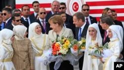 Kanselir Jerman Angela Merkel (tengah) dan Presiden Dewan Uni Eropa Donald Tusk (kanan) berbicara pada gadis-gadis muda di kamp pengungsi Nizip di provinsi Gaziantep, Turki (23/4). (AP/Lefteris Pitarakis)