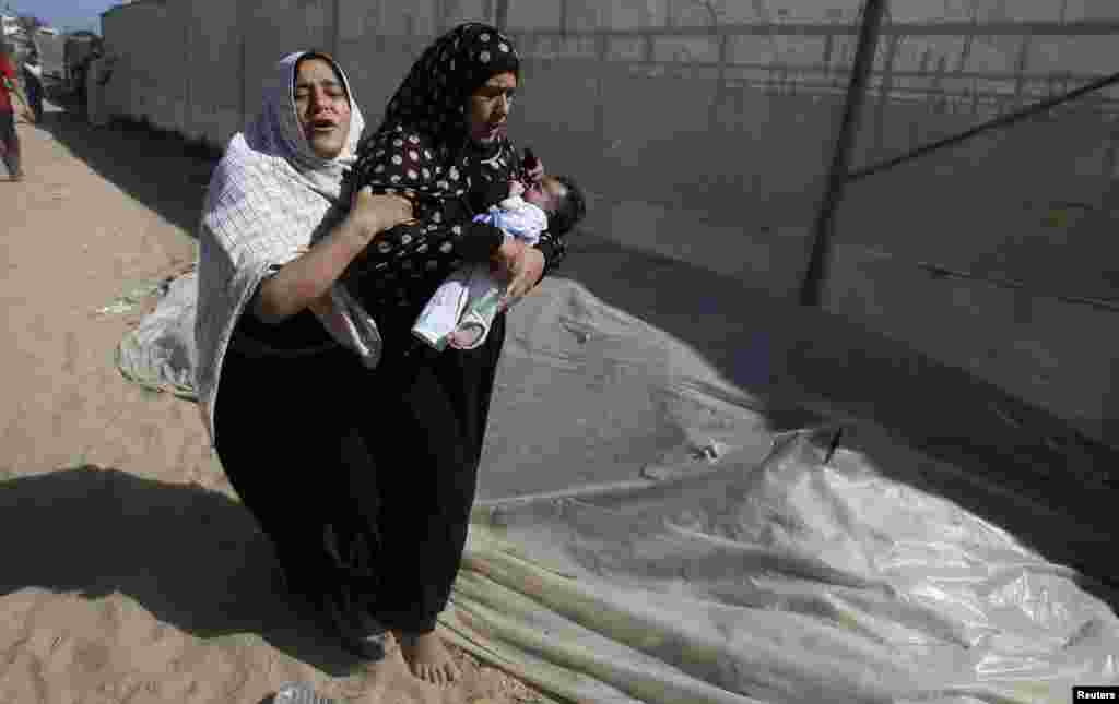 Palestinians flee their houses following what witnesses said was an Israeli air strike on a nearby house in Khan Younis in the southern Gaza Strip.
