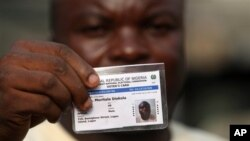 Muritala Diekola, display his new voters registration card in Lagos, Nigeria, Saturday, Jan. 15, 2011. An effort to register 70 million voters across Nigeria before its April presidential election wobbled to a start Saturday, as volunteers fought with mal