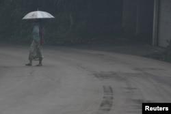 A woman uses an umbrella as she walks through ash from Mount Agung volcano during an eruption in Bebandem Village, Karangasem, Bali, Indonesia, Nov. 26, 2017.