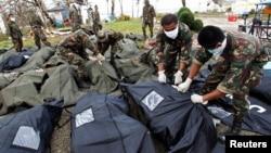 菲律賓中部颱風災區獨魯萬11月13日屍體在親屬認證後被士兵放入屍袋中。