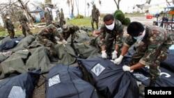 Para tentara menutup kantong jenazah korban topan Haiyan setelah diidentifikasi oleh keluarga mereka di kota Tacloban, Filipina Tengah (13/11).