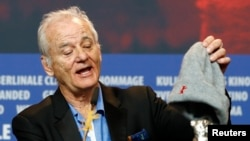 "Actor Bill Murray shows the Silver Bear for Best Director award for Wes Anderson for movie ""Isle of Dogs"" at the news conference after the awards ceremony at the 68th Berlinale International Film Festival in Berlin, Germany, Feb. 24, 2018."