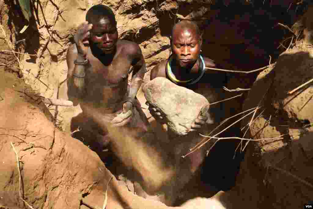 Two artisanal miners dig a pit in a dry riverbed in Karamoja, Uganda, March 2, 2014. (Hilary Heuler for VOA)