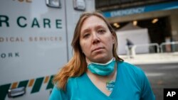 Registered Nurse Elizabeth Schafer, 36, of South St. Paul, Minn., stands for a portrait before entering Beth Israel Mount Sinai Hospital for her second day volunteering to combat the COVID-19 pandemic, Wednesday, April 1, 2020, in New York. (AP Photo/John Minchillo)