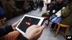 A man tries to get connected to the YouTube web site with his tablet at a cafe in Istanbul, March 27, 2014.