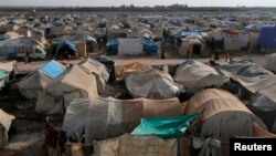 Residents walk past tents at the Bab Al-Salam refugee camp in Azaz, near the Syrian-Turkish border, Nov. 19, 2014.