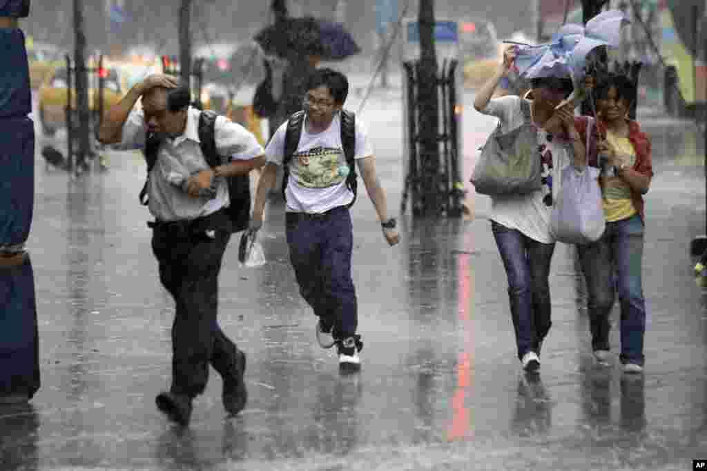Du khách trốn gió lớn của bão Saola ở Đài Bắc, Đài Loan, 1/8/2012.