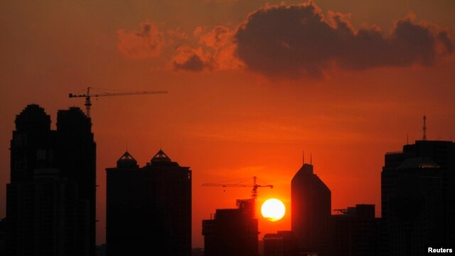 FILE - The sun sets behind buildings under construction in Guangzhou, Guangdong province.