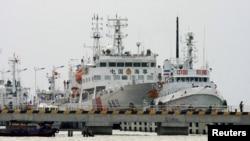 "Kapal patroli terbesar China di Laut China Selatan, ""Haixun 31"" (tengah) di Sanya, provinsi Hainan, sebelum pergi untuk melakukan pencarian pesawat Malaysia Airlines yang hilang (9/3)."