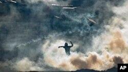 Một người biểu tình chống chính phủ trong thủ đô Caracas của Venezuela, đứng giữa đám khói hơi cay mịt mù, ném đá về hướng Vệ binh Quốc gia, 16/3/14