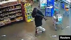 Gunman aims rifle inside store during attack on Westgate shopping mall, Nairobi, Sept. 2013.