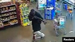 A gunman aims his rifle inside a store during an attack on the Westgate shopping mall in this still frame taken from video footage by security cameras inside the mall in Nairobi and released to Reuters on Oct. 17, 2013.