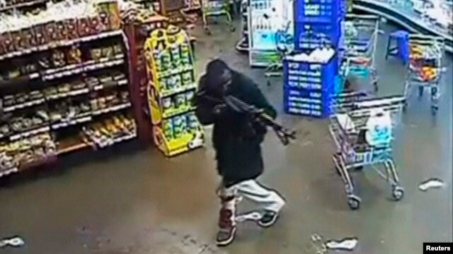 FILE - A gunman aims his rifle inside a store during an attack on the Westgate shopping mall in this still frame taken from video footage by security cameras inside the mall in Nairobi and released to Reuters on Oct. 17, 2013.